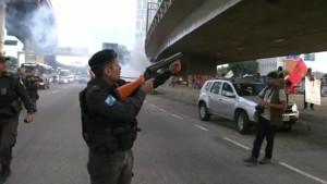 Rio de Janeiro Rio de Janeiro, 7h37 PM saca arma não letal próximo a manifestantes em local onde foi jogada bomba de efeito moral - Foto Reprodução TV Globo